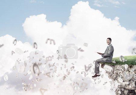 Photo pour Jeune homme d'affaires assis sur le bord d'une falaise avec livre rouge dans les mains - image libre de droit