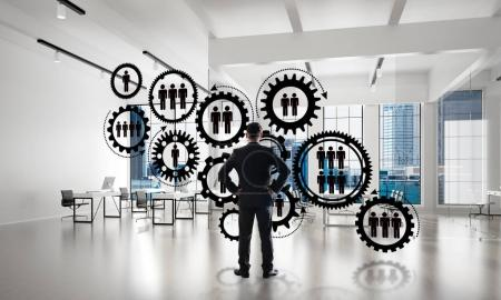 Elegant businessman in modern office interior with social connection concept, Mixed media