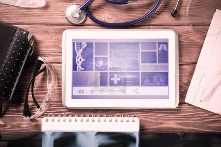 Photo for White tablet pc and doctor tools on wooden table - Royalty Free Image