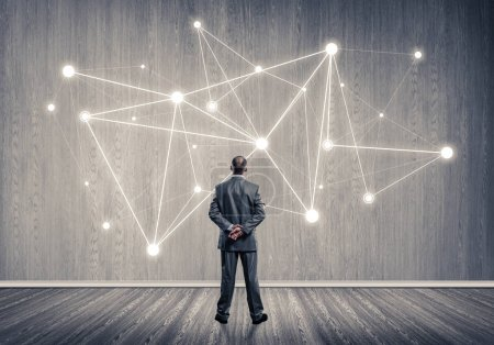 Photo for Back view of businessman looking at wall with drawn social connection concept - Royalty Free Image