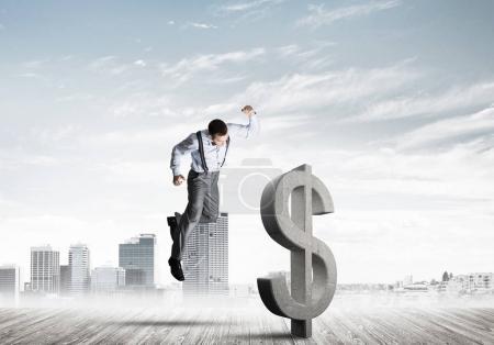 Determined banker man against modern cityscape breaking dollar concrete figure