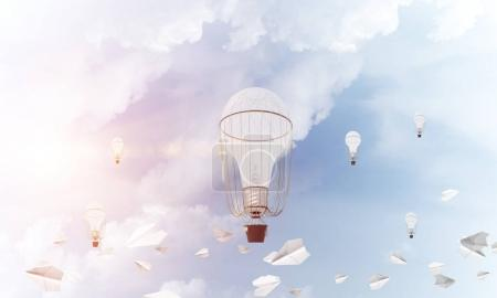 Colorful aerostats flying among paper planes and over the blue cloudy sky. 3D rendering.