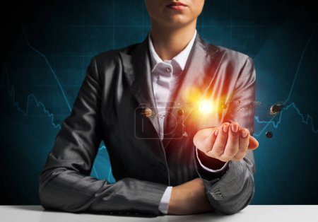Businessman in suit presenting glowing solar system in his hands with dark blue wall on background. 3D rendering.