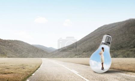 Photo pour Jeune femme d'affaires piégée à l'intérieur de l'ampoule sur la route de campagne - image libre de droit
