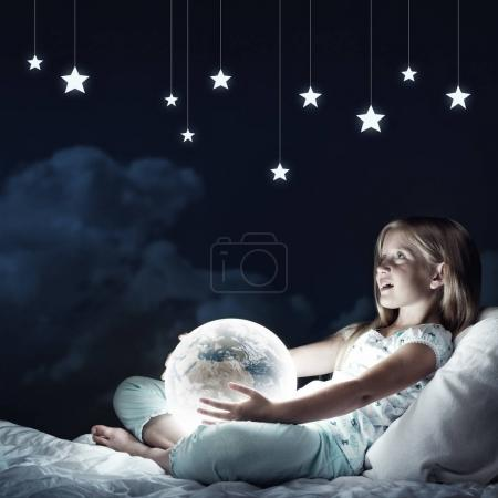 Photo for Cute girl sitting in bed with Earth planet - Royalty Free Image