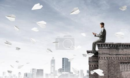 Young businessman sitting on building top