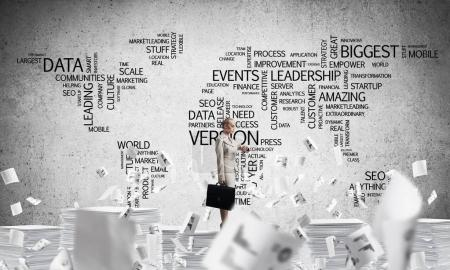 Business woman in suit standing among flying documents with business-related terms in form of world map on background. Mixed media.