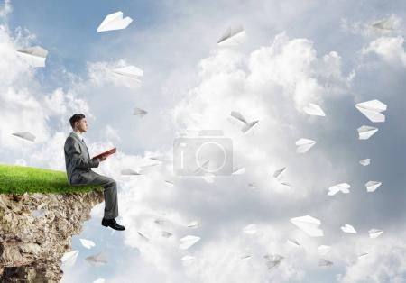 Young businessman sit on edge of a cliff in blue sky with red book in hands