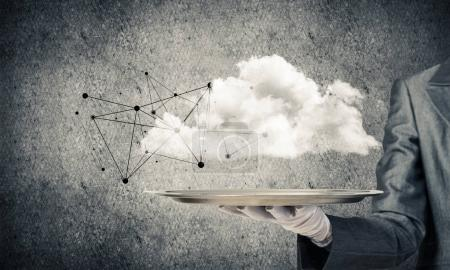 Photo for Cropped image of waitress's hand in white glove presenting cloud with social media network structure on metal tray. Gray wall on background. 3D rendering. - Royalty Free Image