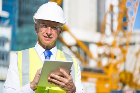Senior engineer man in suit and helmet working on tablet pc on construction site at sunny day