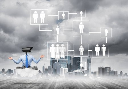 Elegant businessman outdoors floating on cloud with camera instead of head against modern cityscape
