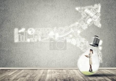 Photo pour Femme d'affaires piégée à l'intérieur de l'ampoule dans une pièce vide en béton avec des croquis d'entreprise sur le mur - image libre de droit