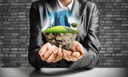 Businessman in suit keeping green island with skycraper city in hands with gray brick wall on background.