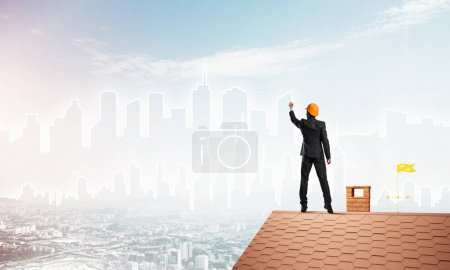 Engineer man standing on house roof