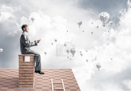 Young businessman sitting on house roof
