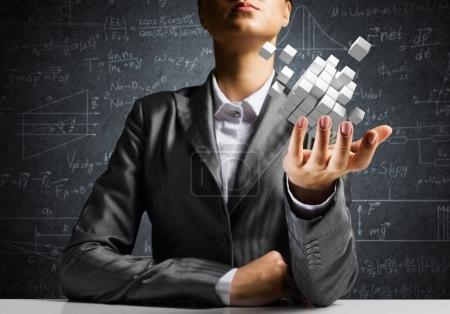 Cropped image of business woman in suit presenting multiple cubes in hand as symbol of innovations. Business sketches on background.