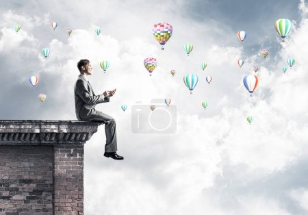 Young businessman sitting on building top with smartphone in hands