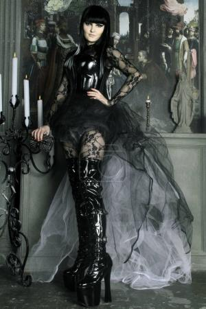 pretty young gothic girl wearing black pvc and lace clothes posing with candles in the old castle