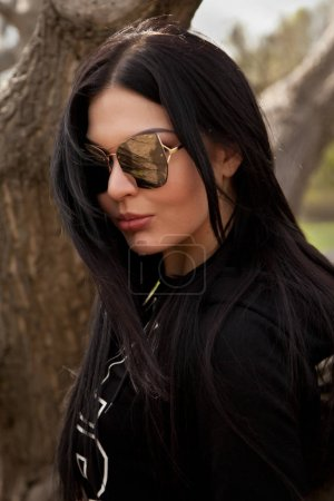 pretty young brunette woman wearing jeans and black shirt with big mirror sunglasses posing near the tree in the park