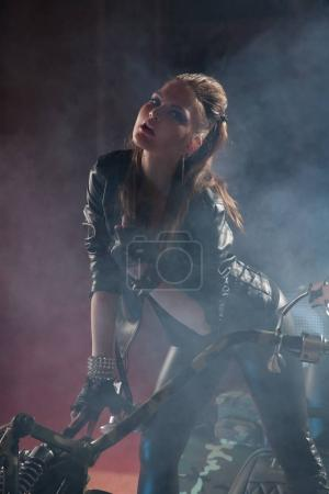 beautiful photomodel wearing leather clothes and posing with unique bike at the night