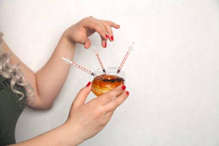Photo pour Gros plan sur le médecin femme faisant l'injection en utilisant une seringue de diabète dans un beignet - image libre de droit