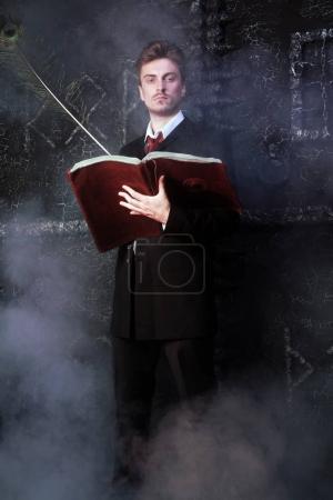 Photo pour Beau écrivain mystique debout sur fond noir dans la fumée - image libre de droit