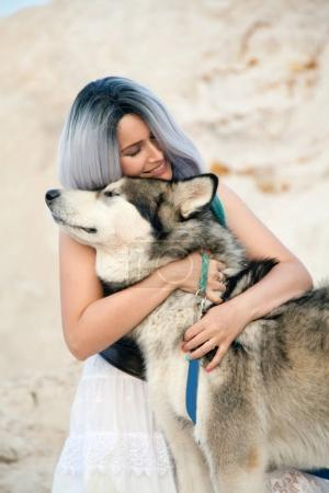 beautiful young woman owner and her lovely happy dog malamute in the desert quarry white sand