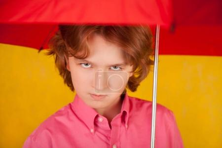 cute kid with red bright umbrella on yellow background alone