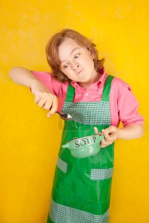 nice child wearing green kitchen apron standing with soup plate and a spoon