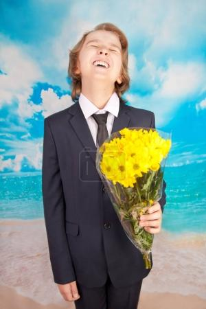 emotional boy with yellow flowers on blue sea background