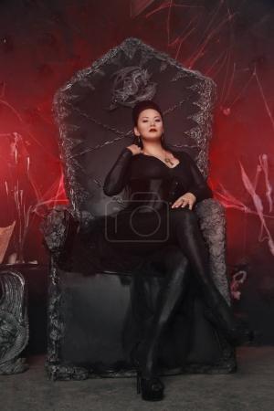 Photo pour Charmante sorcière maléfique dark femme port élégant robe gothique et assis sur la chaise de reine noir énorme - image libre de droit