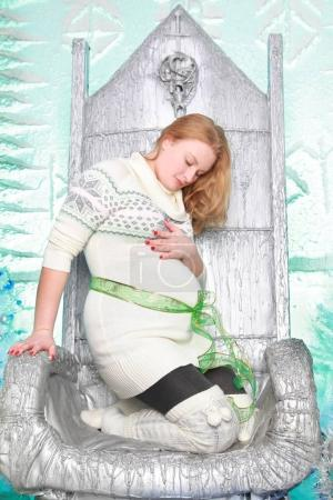 pretty happy pregnant woman wearing white sweater and sitting on the xmas chair with christmas tree and new year gift boxes