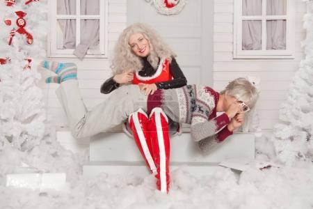 Photo pour Chaud Santa fille punit un nerd homme dans des lunettes et nouvelle année pull, le frappe sur le cul sur le fond de neige maison de Noël - image libre de droit