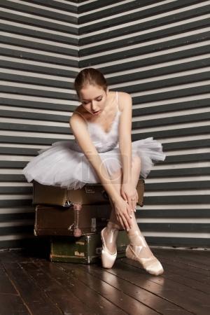 Photo pour C'est une jolie jeune ballerine dans une robe classique blanche assise sur une pile de valises rétro sur un fond rayé noir et blanc - image libre de droit