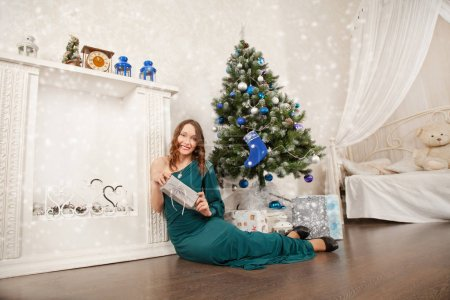 pretty cute teenager girl posing in evening dress near a Christmas tree and the white fireplace at her home
