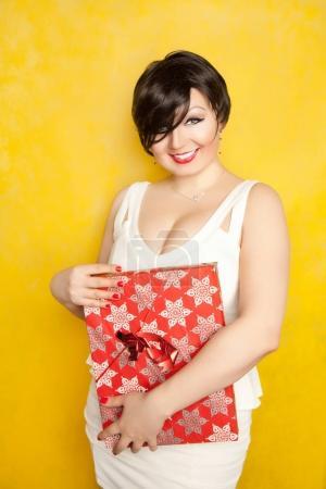 Photo pour Très positive belle riant brune aux cheveux courts est vêtue d'une robe blanche serrée et maintenant cadeau rouge sur fond jaune - image libre de droit