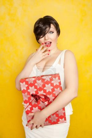 very positive beautiful laughing brunette with short hair is wearing a tight white dress and holding red gift on yellow background