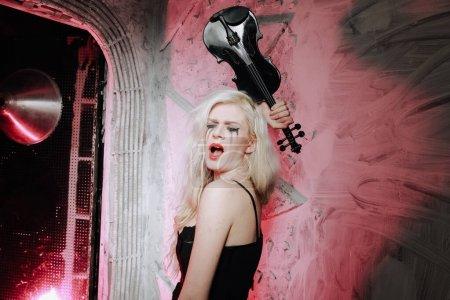 Photo pour Fille gothique blonde avec violon sur fond blanc. Jeune femme sur la fête - image libre de droit