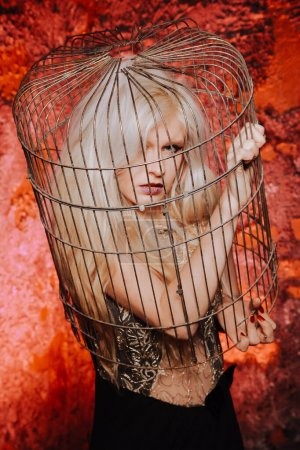 Photo for The woman voluntarily climbed into the cage. the psychology of a victim - Royalty Free Image