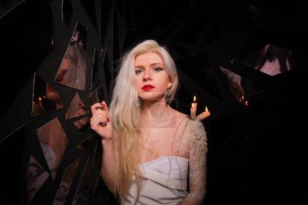 chica mística con velas que se paran en la cera en la piel de las niñas