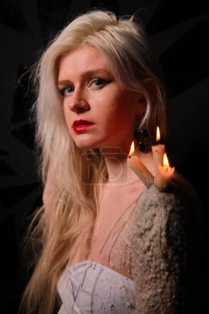 Mystical girl with candles that stand on wax on th...