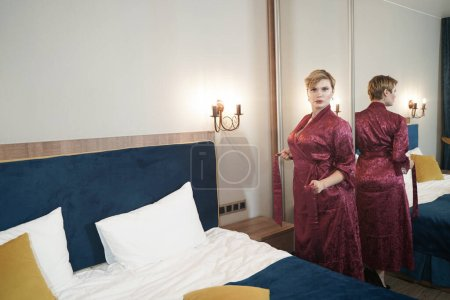 Photo pour Stylish pin up short hair blonde woman with plus size curvy body posing in fashion red bathrobe near the mirror in the bedroom alone. - image libre de droit