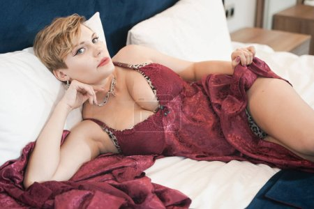 Photo pour Stylish pin up short hair blonde woman with plus size curvy body posing in fashion red bathrobe in the bedroom alone. - image libre de droit