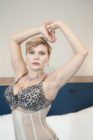 Photo pour Stylish pin up short hair blonde woman with plus size curvy body posing in fashion leopard underwear in the bedroom alone. - image libre de droit