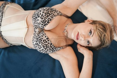 Photo for Stylish pin up short hair blonde woman with plus size curvy body posing in fashion leopard underwear in the bedroom alone. - Royalty Free Image