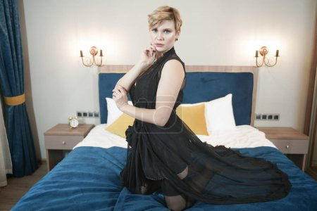 Photo pour Stylish pin up short hair blonde woman with plus size curvy body posing in fashion underwear in the bedroom alone. - image libre de droit