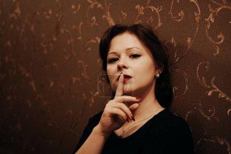 Photo pour Belle dame en robe rétro face au mur noir seule. - image libre de droit