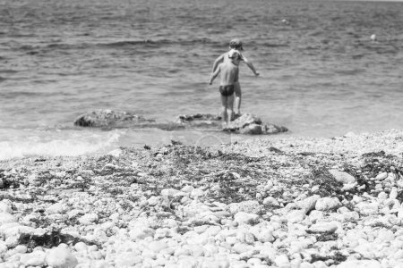 Photo pour Les petits garçons jouent à la côte de la mer avec une photo de la plage, noir et blanc caillou pierres - image libre de droit