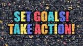 Set Goals Take Action on Dark Brick Wall.