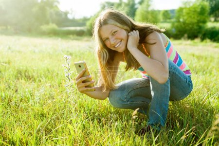Photo for Young teenage girl using a smartphone, photographing a flower in a park. For your page in the instagram - Royalty Free Image